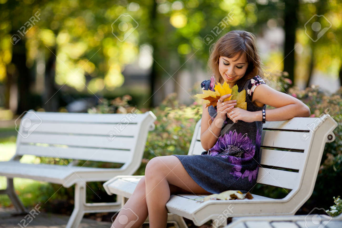 Lonely girl siting on a bench in an autumn park Stock Photo - 10787212