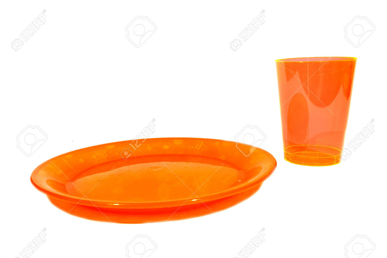 isolated orange plastic cup and plate used for food and drink stock