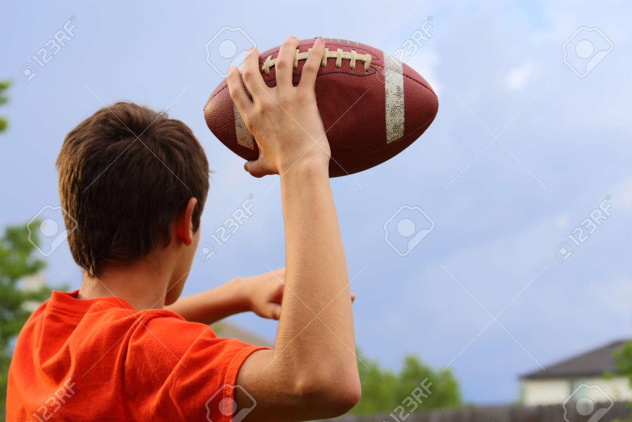 Foto de archivo - Un joven inclinando el brazo hacia atrás y se prepara  para lanzar una pelota de fútbol 7cadd987306a