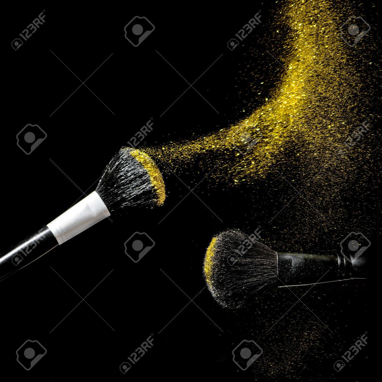 Make-up brush with gold powder explosion on black background. - 140592666