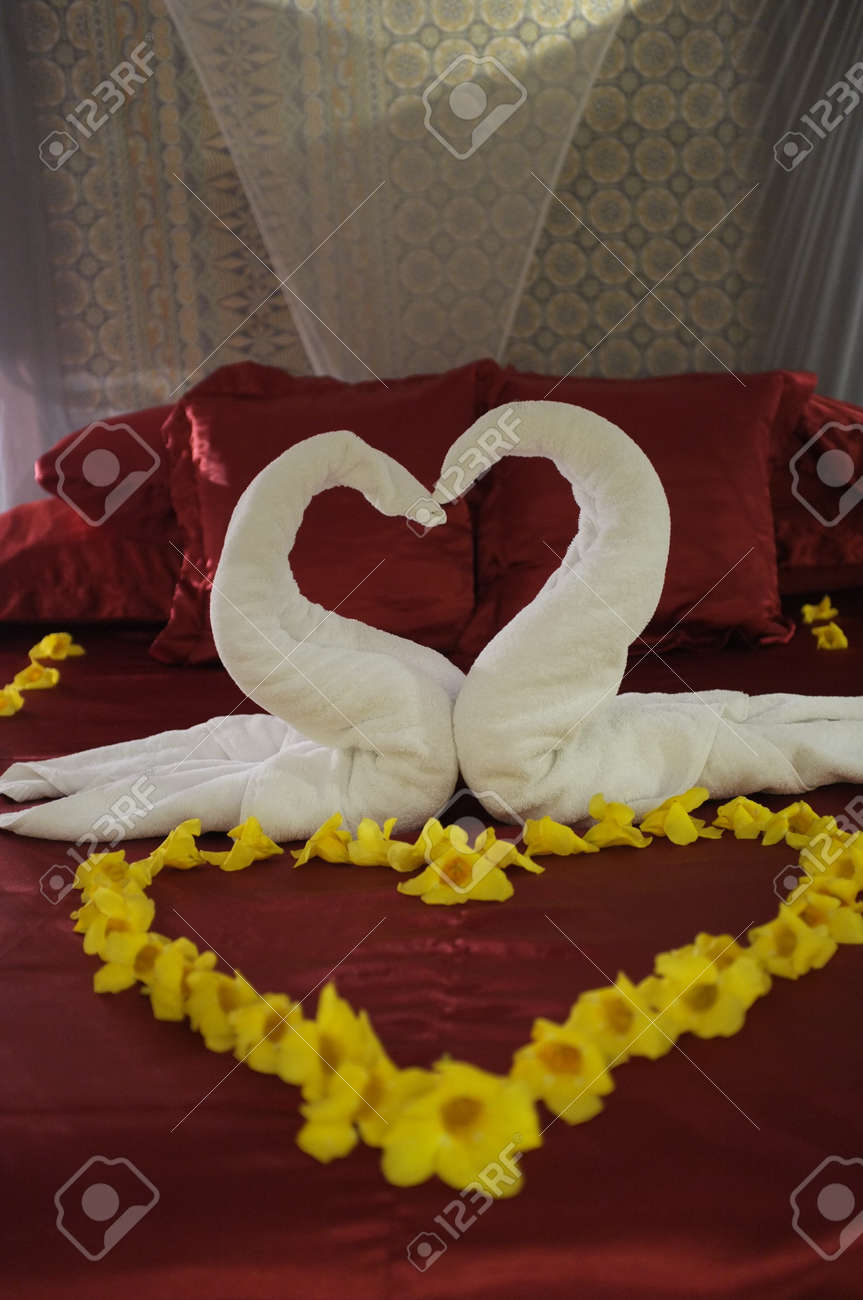 Heart shaped towel decoration on bed Stock Photo  32186811