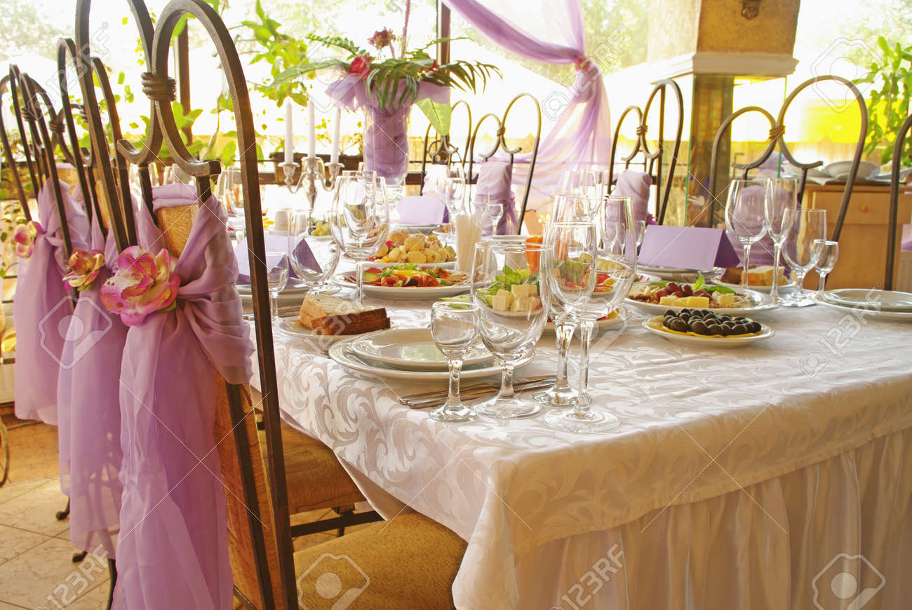 Table set for a wedding dinner decorated with flowers and a silk bow Stock Photo - 8551023