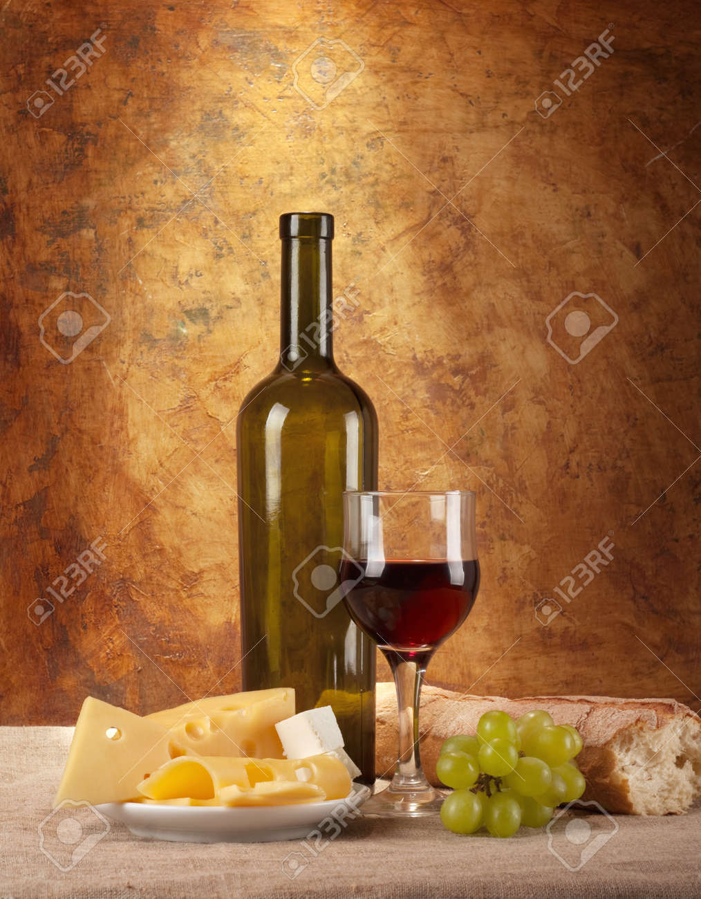 Red wine, assorted cheeses, bread and grapes in a still life setup. Stock Photo - 9767802