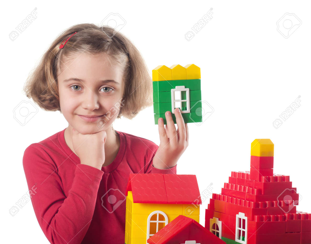 Cute little girl is constructing a house using building blocks Stock Photo - 13338436