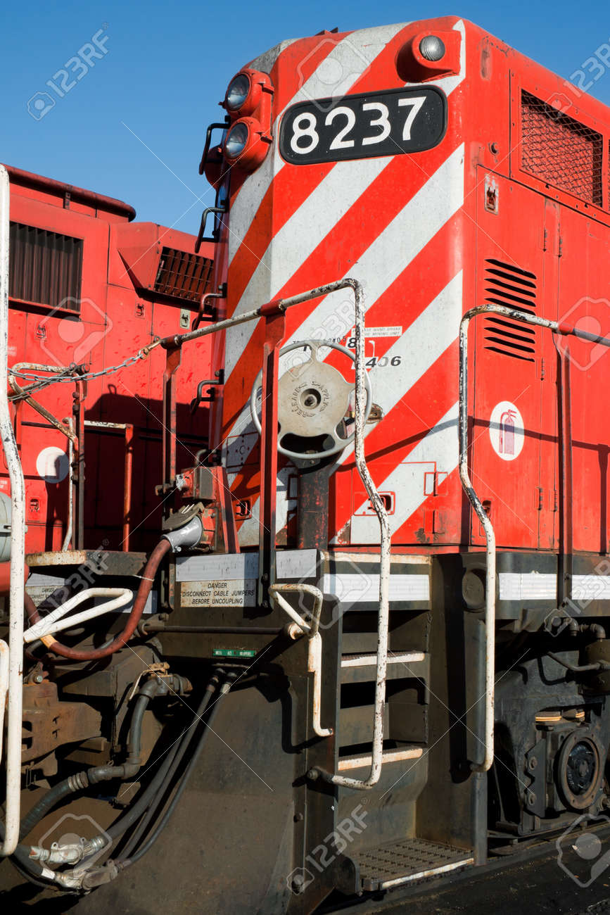 Detail of a front heavy diesel north American locomotive, with headlights, red and white stripes, stairs, connections, hand brake wheel    Stock Photo - 20552175