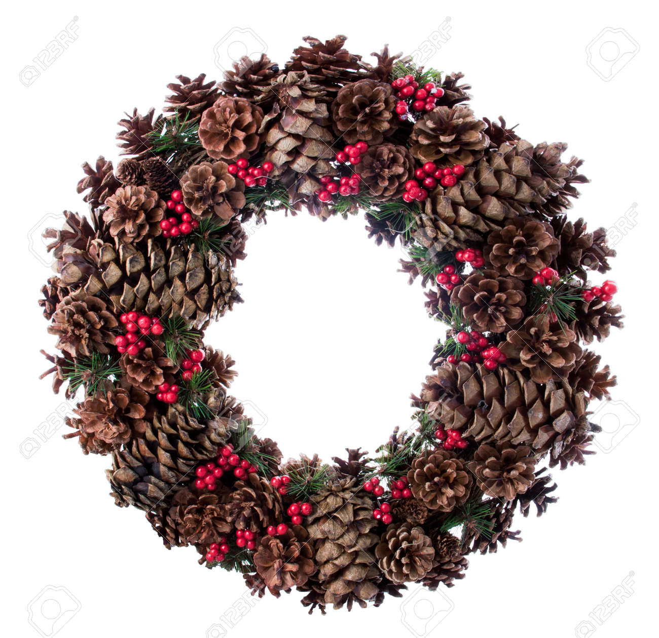 Christmas wreath made it by fir tree cones little red berry fruits and branches isolated in white Stock Photo - 20554053