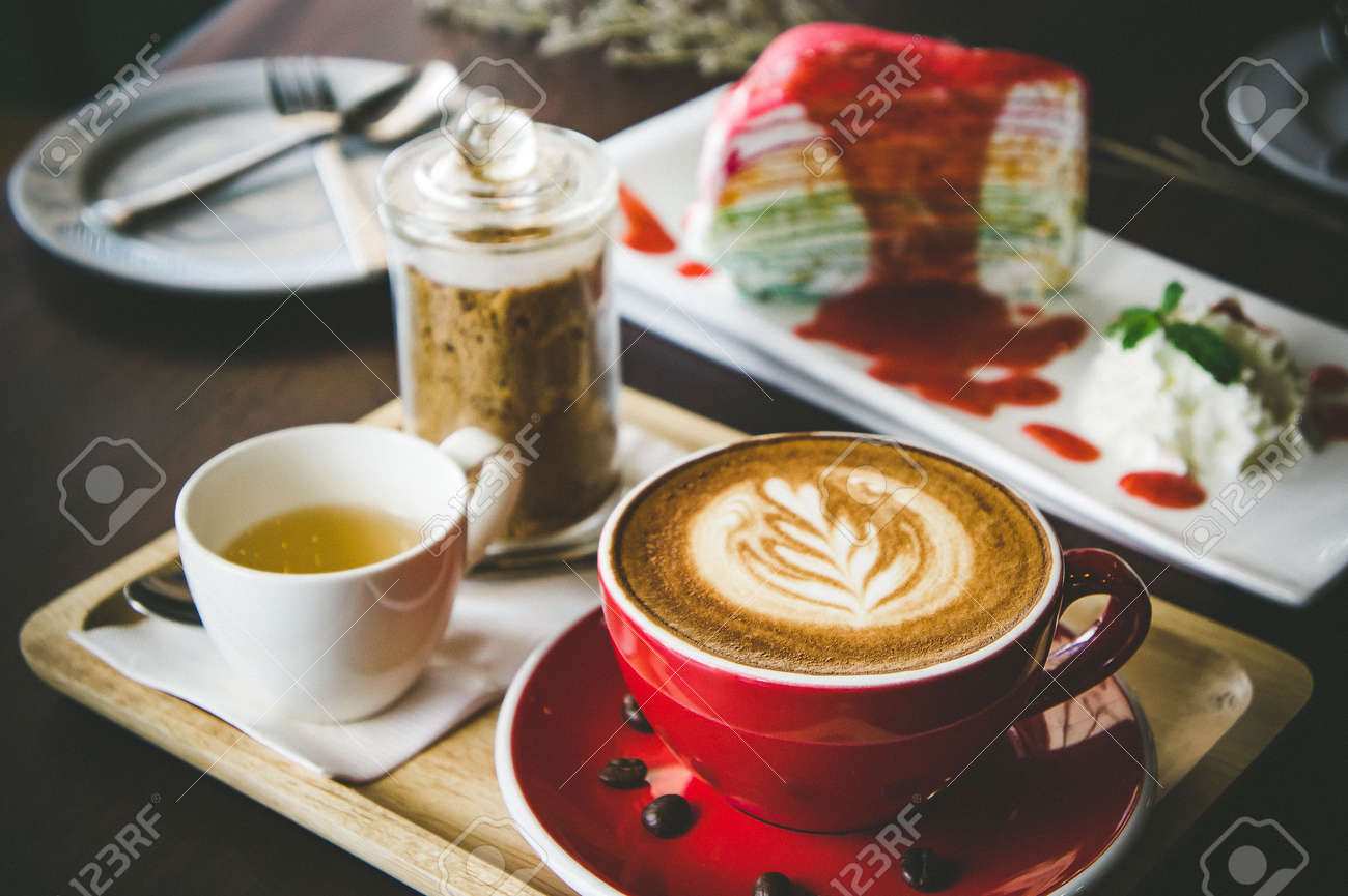 aroma coffee red cup latte art and tasty cake on wood table in coffee shop with vintage dark tone and copy space Stock Photo - 84184298