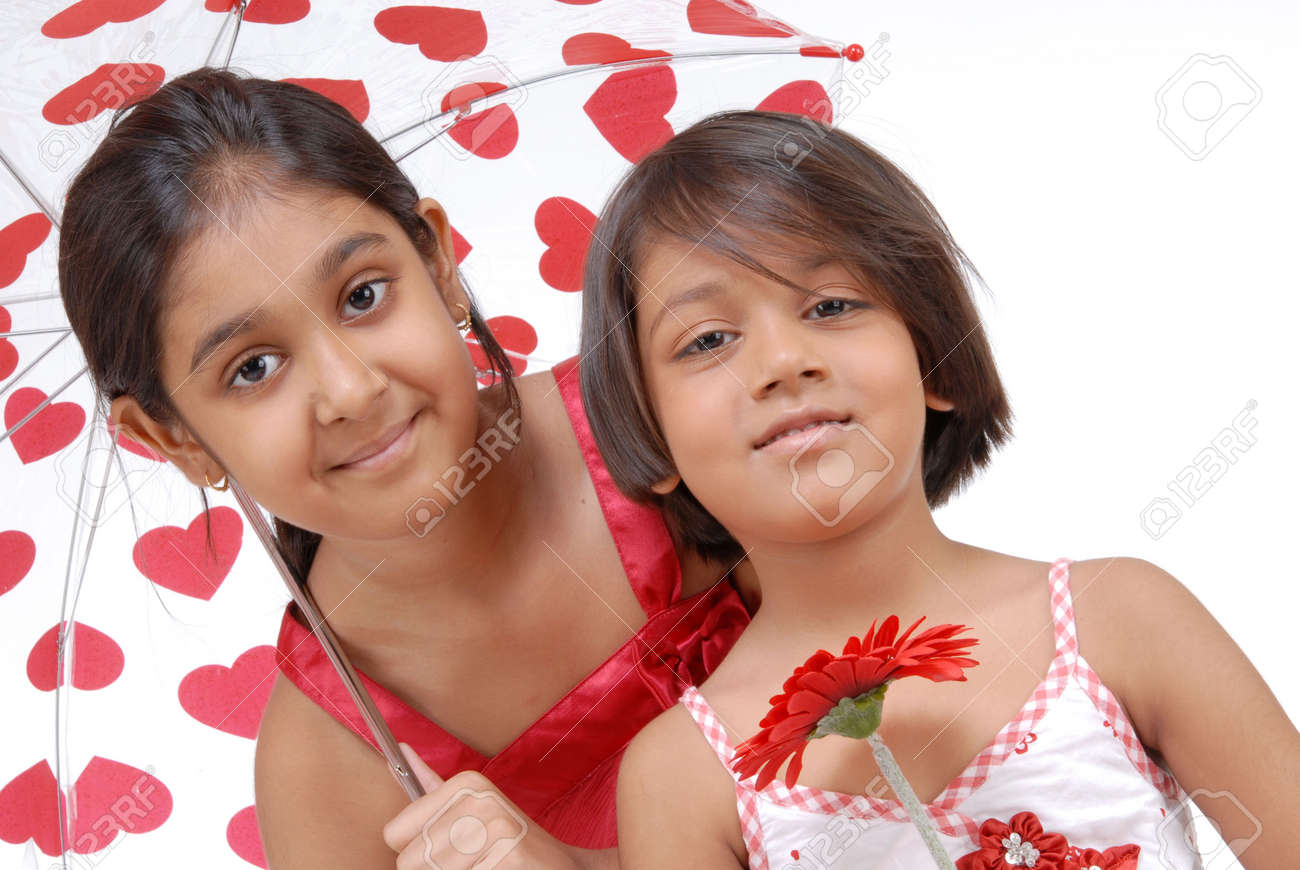 Two Loving Cute Sisters Giving Pose With Umbrella Stock Photo