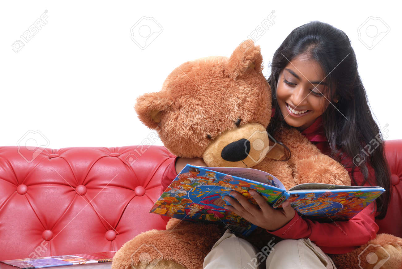 Charming girl reading book with her teddy bear on Red Sofa Stock Photo - 16717857