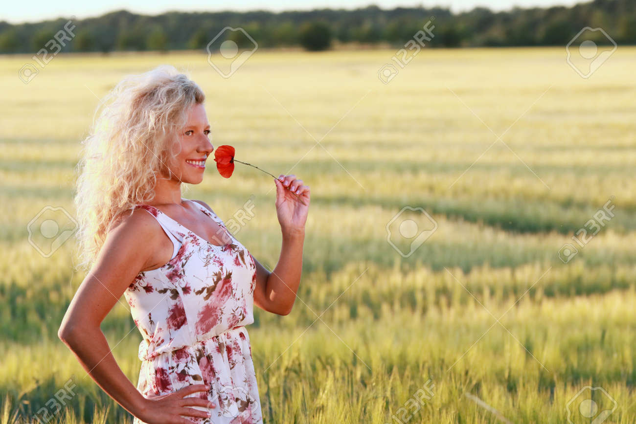 823fb4950924 Happy mature woman with a long dress in summer evening in front of a corn  field