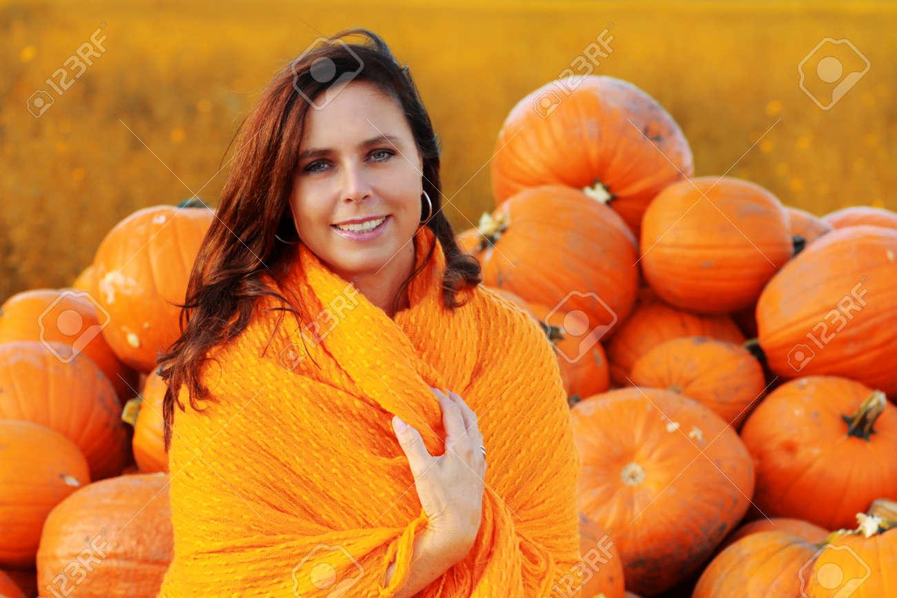 attractive mature woman holding big orange pumpkin in front.. stock