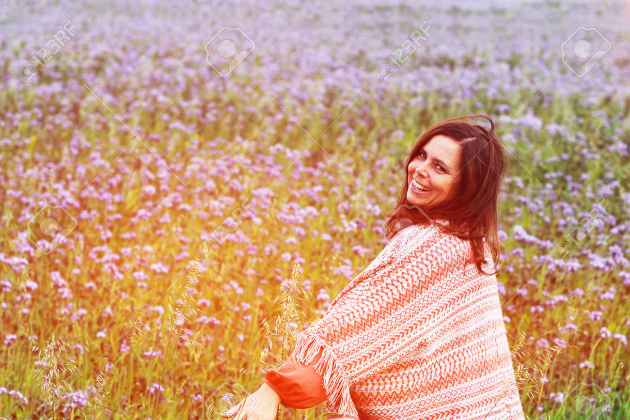 happy mature woman with a big colorful scarf enjoys leisure in