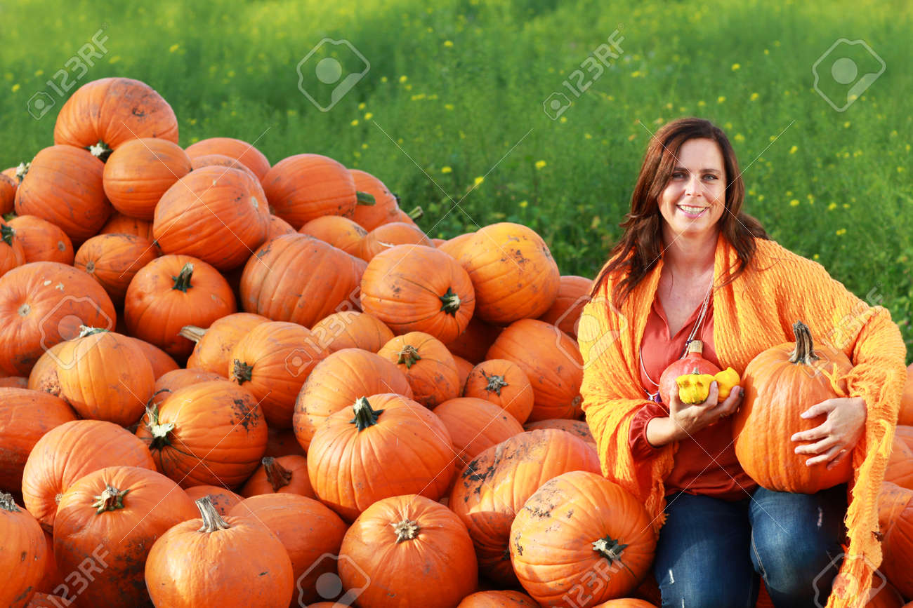 attractive mature woman holding big orange pumpkin in front.. stock