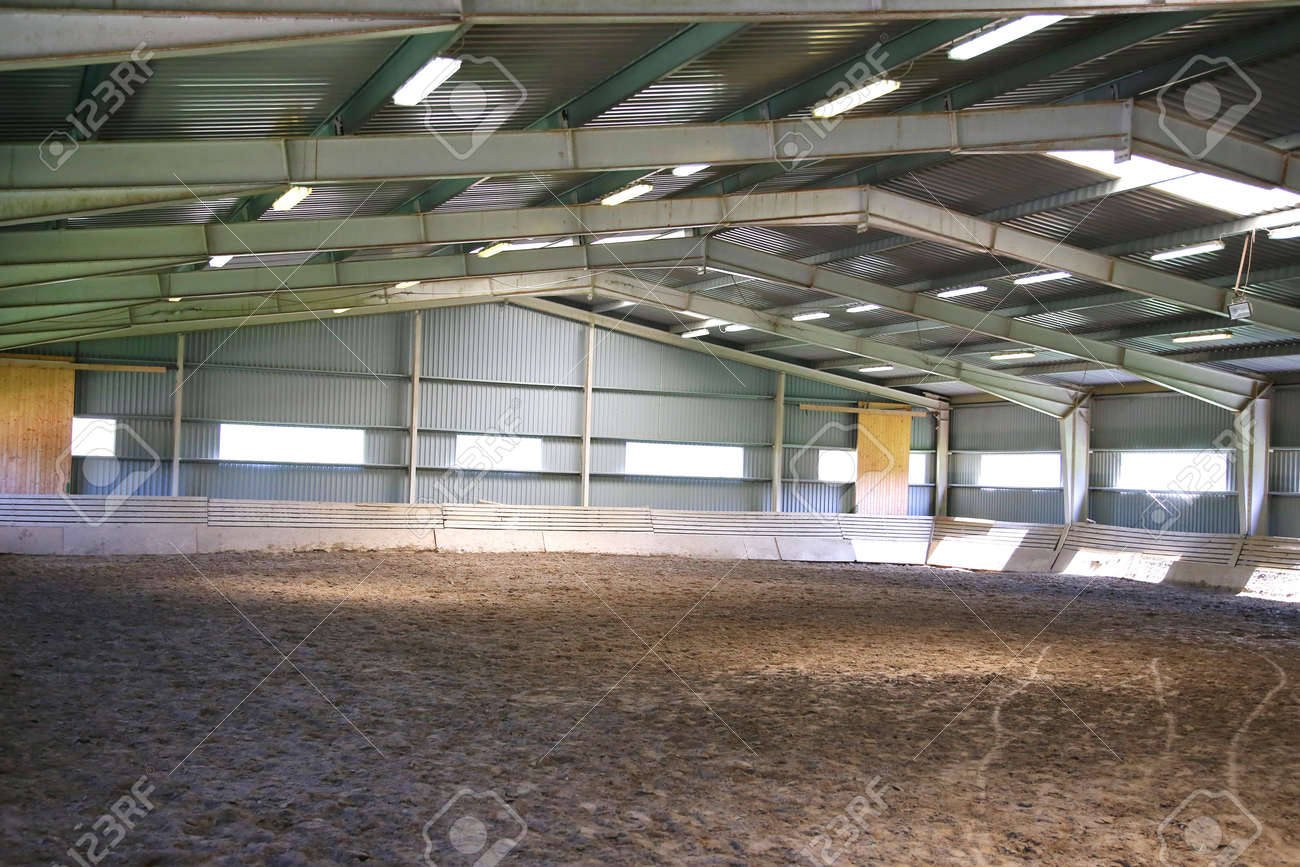View an indoor riding arena backlight with sandy covering