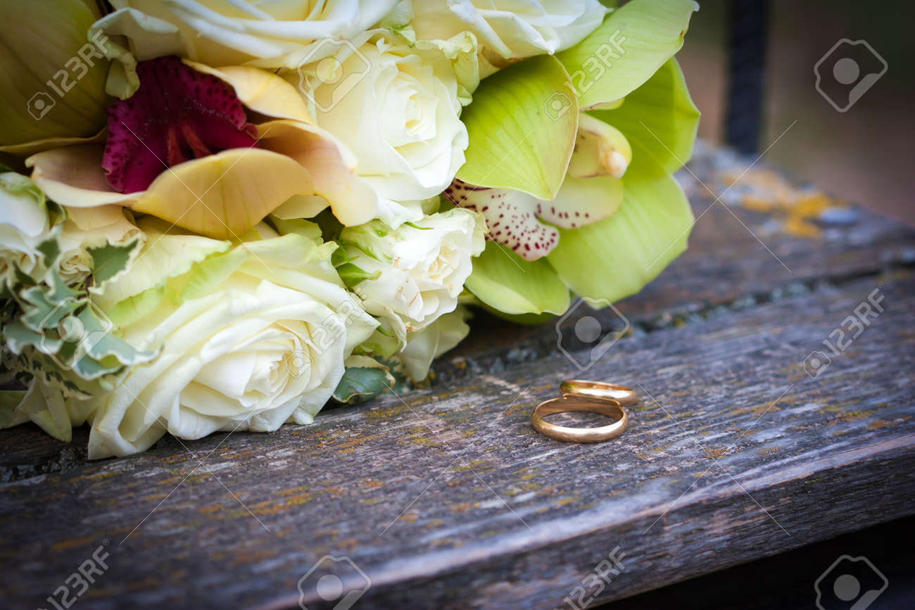 Wedding Rings And White Roses Bouquet Stock Photo