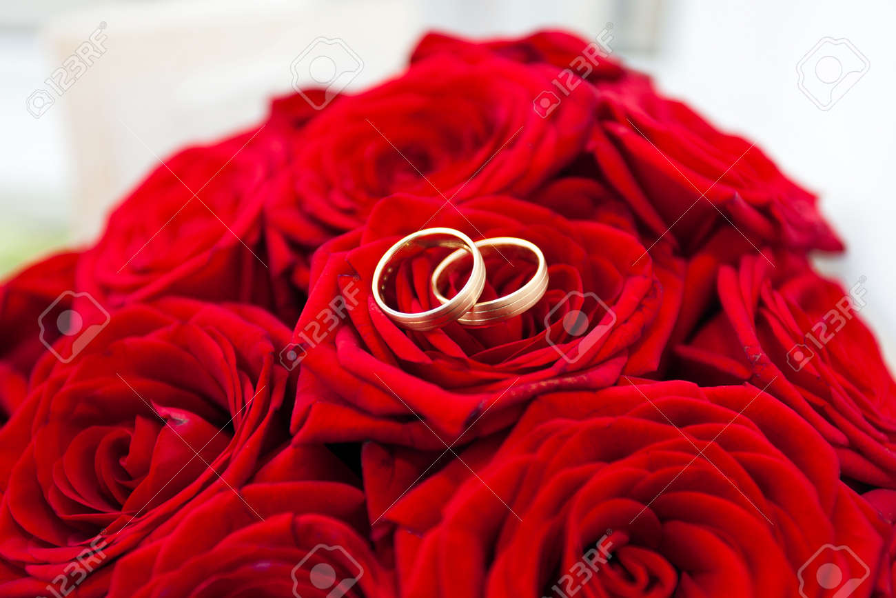 Wedding Rings On Red Roses Bouquet Stock Photo