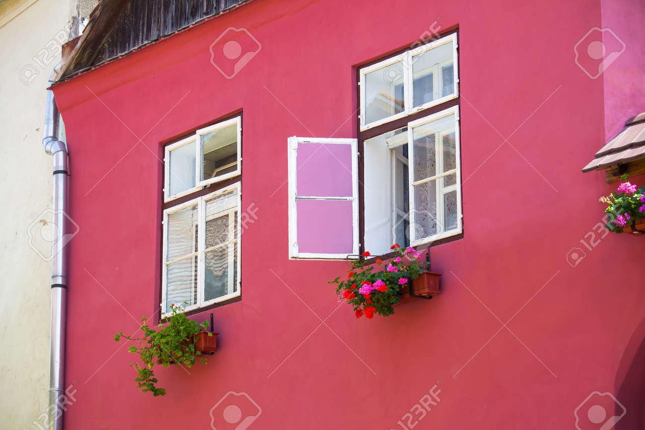 Roze gevel met witte ramen en straatlantaarn op een oud roze huis