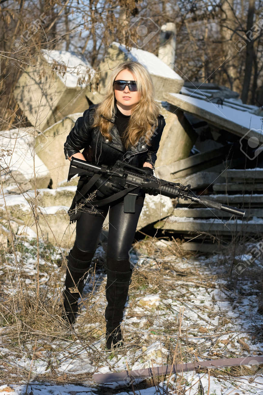 Pretty young blonde with a gun outdoors Stock Photo - 12620941
