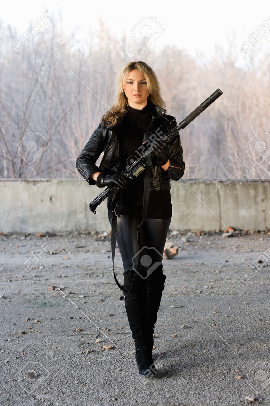 Pretty girl holding a gun in neglected building Stock Photo - 12621398