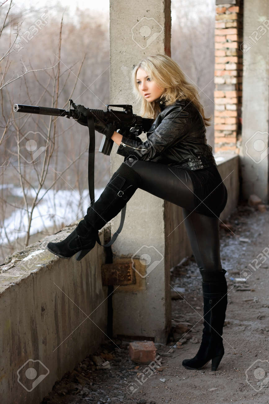 Blond girl on high heels taking a shot with machine gun Stock Photo - 12621178