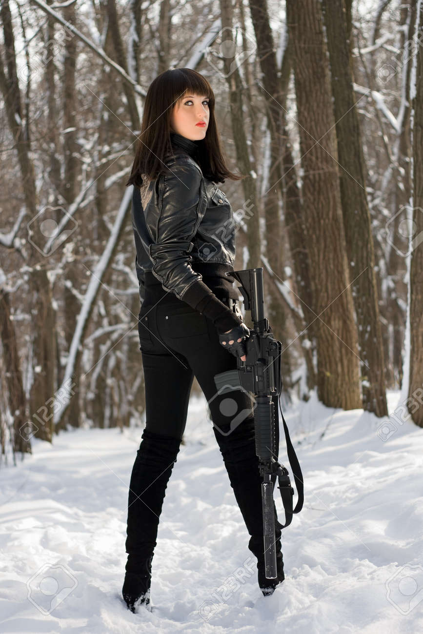 Beautiful young woman with a rifle in winter forest Stock Photo - 12621773