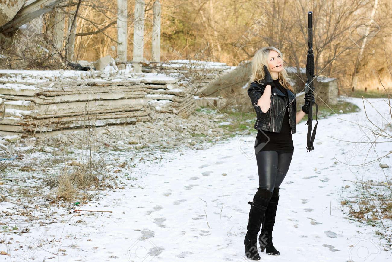 Attractive young woman with a gun outdoors Stock Photo - 12983958