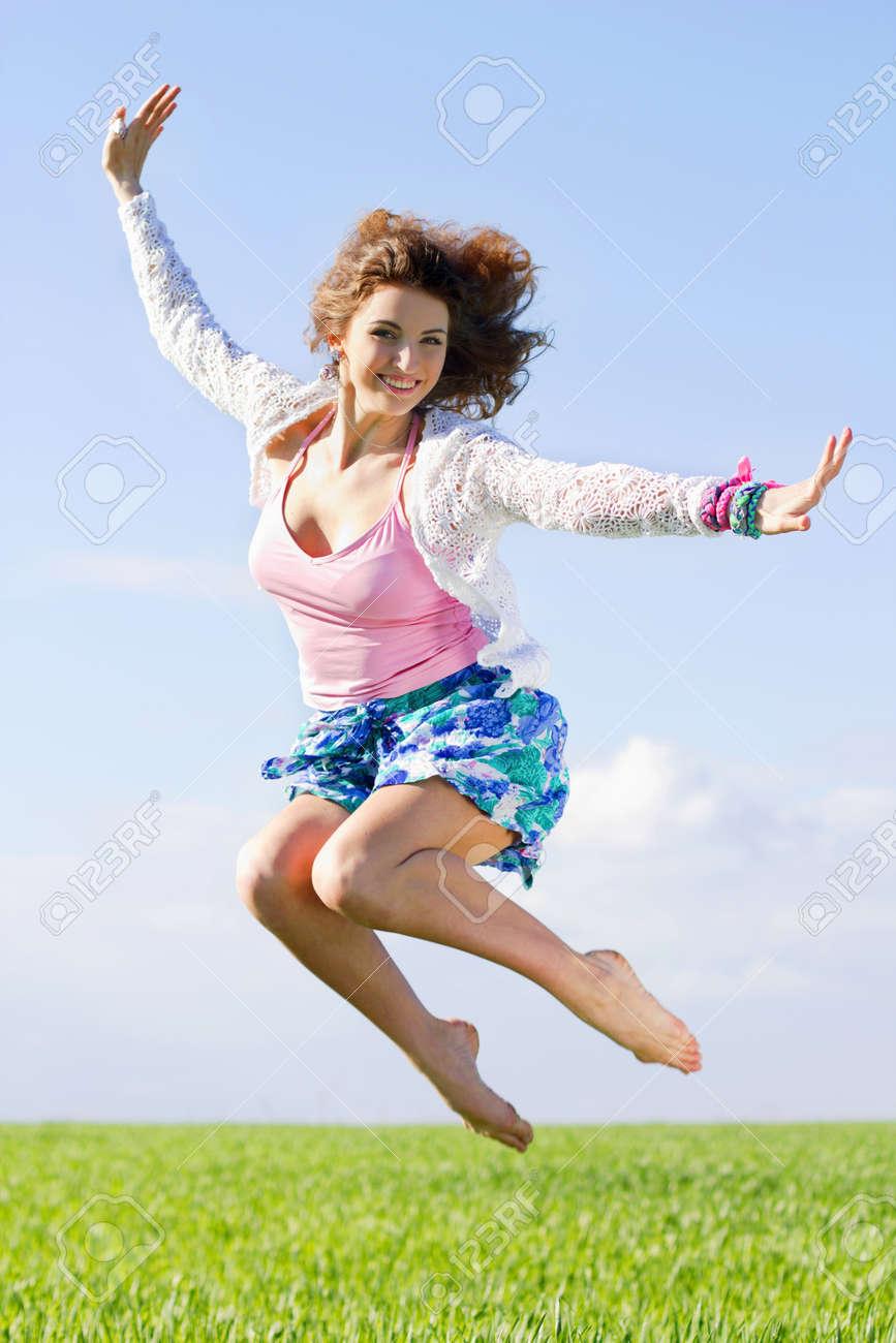 Joyful beautiful young woman in a green field Stock Photo - 15239065