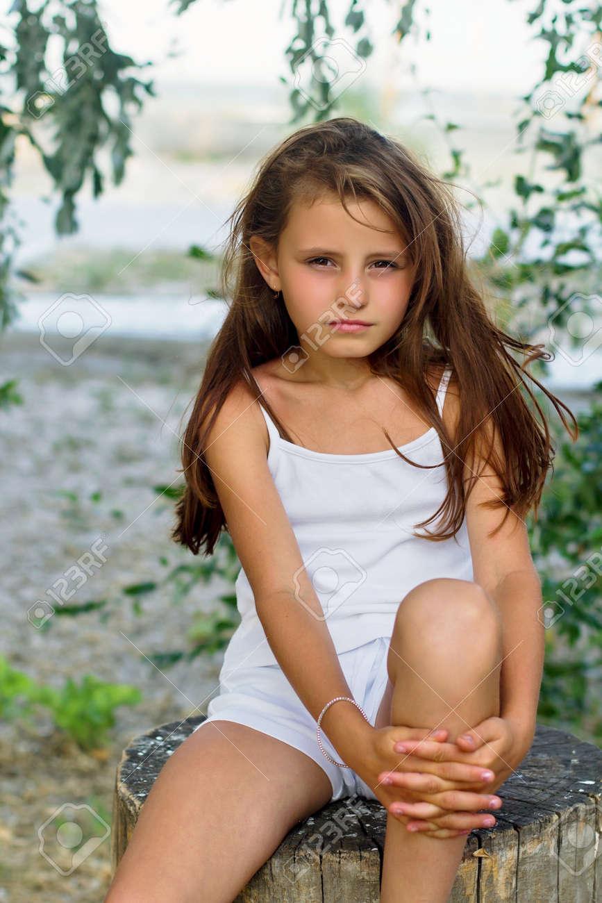 Pretty little girl sitting on a tree stump Stock Photo - 16236029