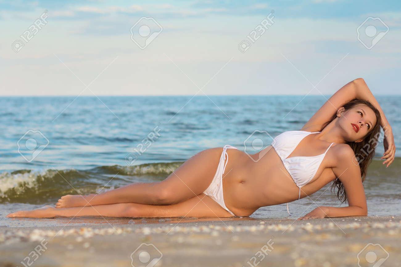 Sexy young woman in white bikini posing on the beach Stock Photo - 20080788