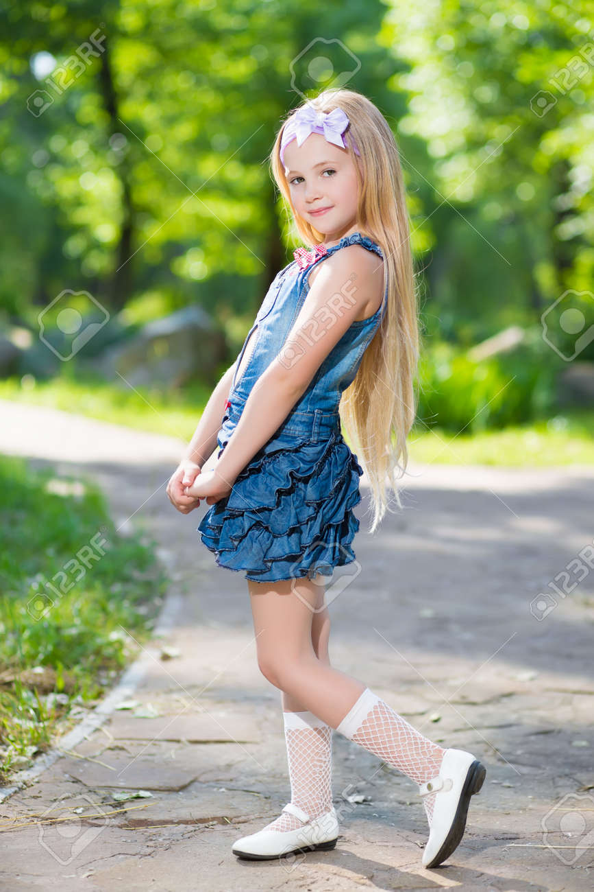 Adorable blond girl posing in jeans dress outdoors Stock Photo - 24181066