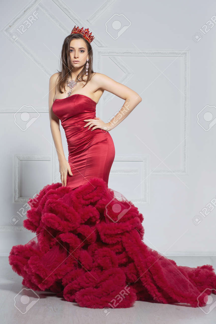Lovely young lady posing in a studio dressed in an elegant red dress and a crown - 128850887