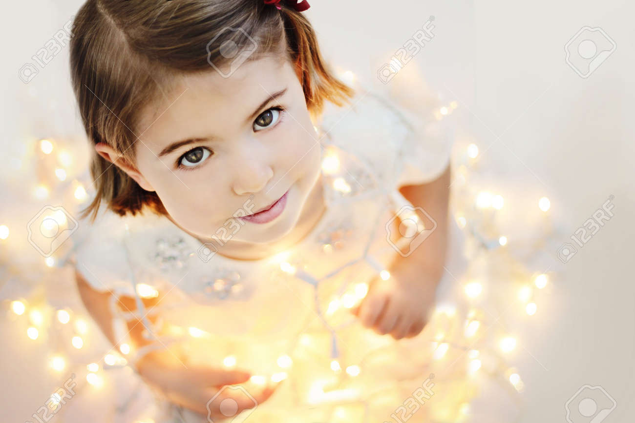 Cute, smiling, happy three years old girl sitting with glowing Christmas lights Stock Photo - 16663482