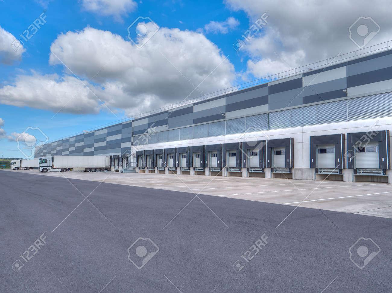 bâtiment industriel moderne et entrepôt avec des camions banque d