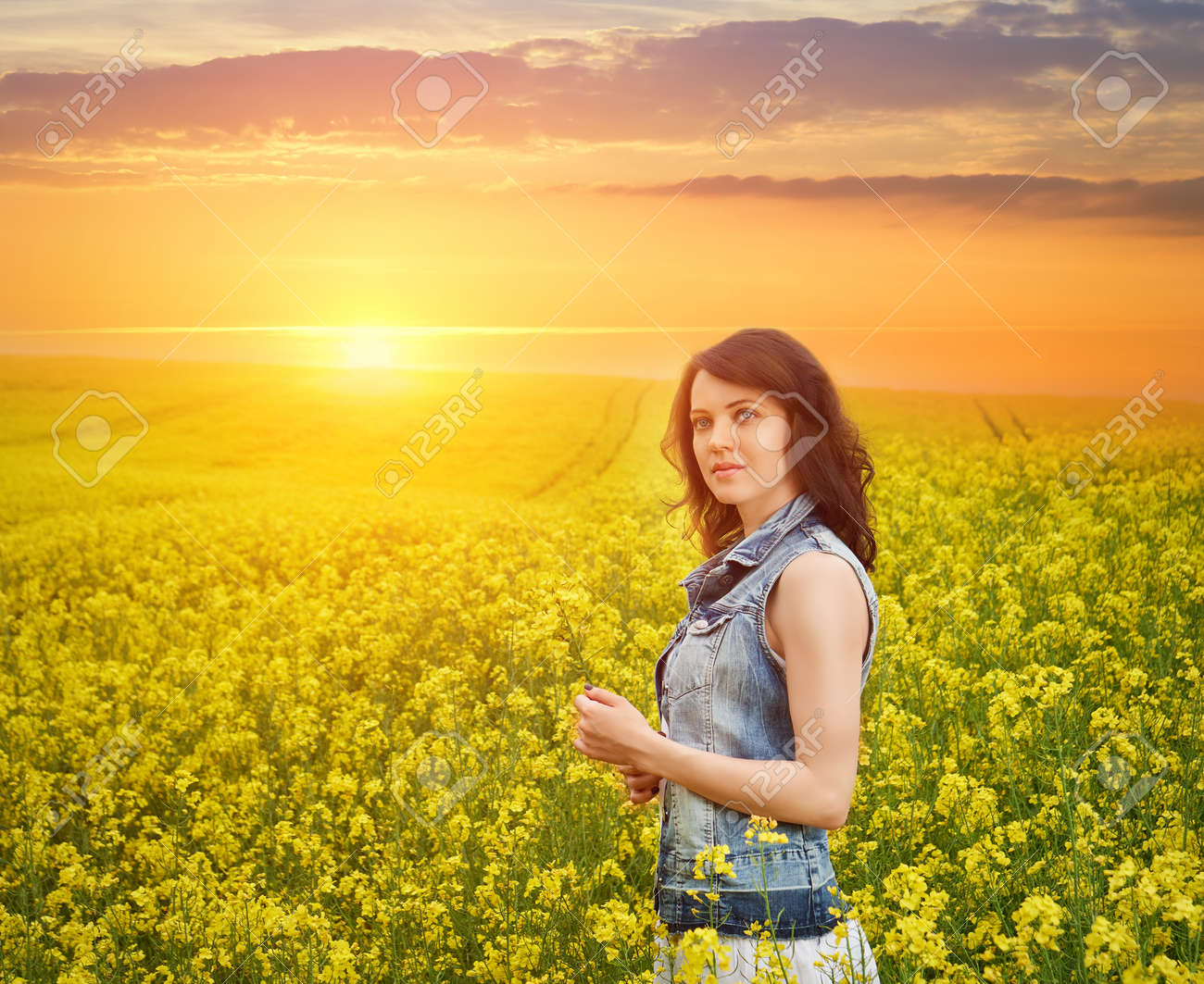 Woman In Field With Yellow Flowers At Beautiful Sunset Fotos
