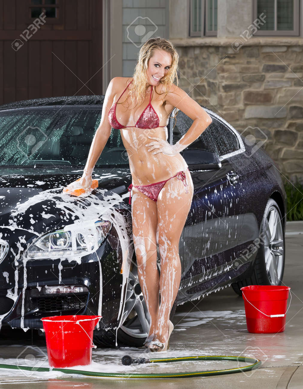 Beautiful bikini models wash a car on a summer day Stock Photo - 14428632