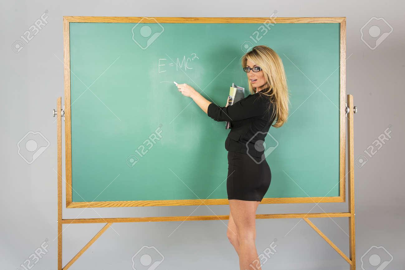 An attractive school teacher in front of a chalkboard