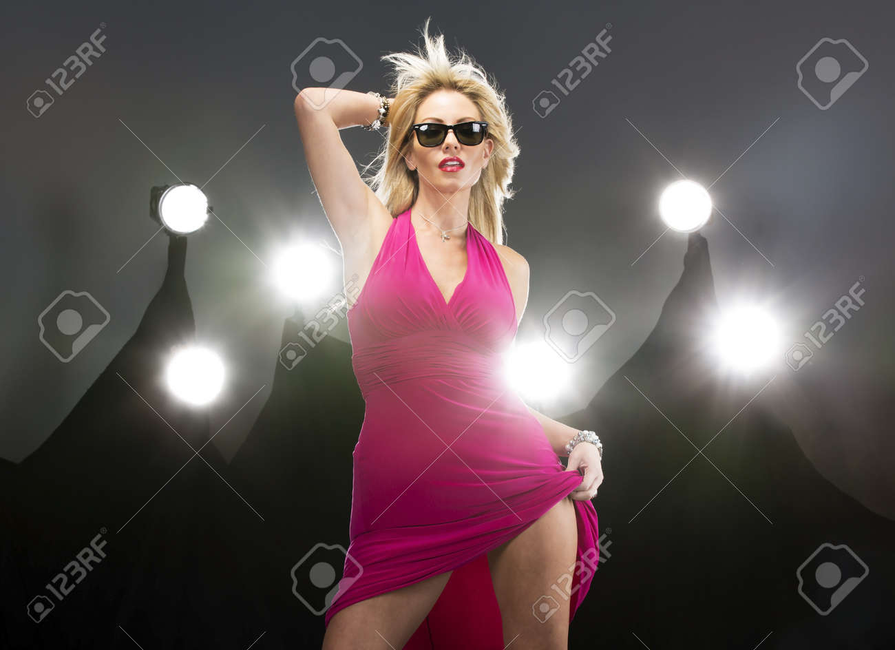 A blonde attractive model poses in a studio environment with lights in the background Stock Photo - 18821475