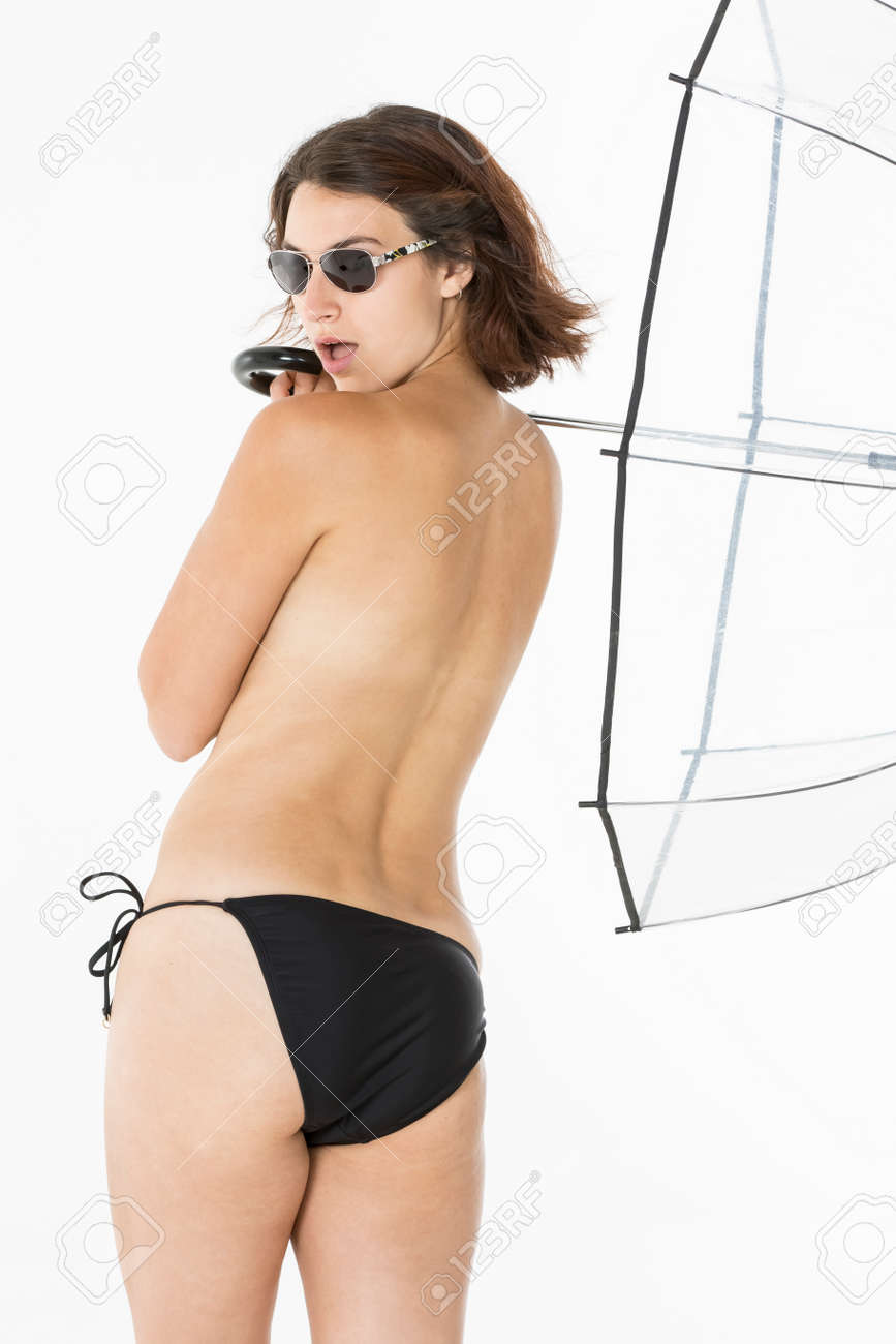 A topless bikini model playing with an umbrella in a studio environment  Stock Photo - 56154670