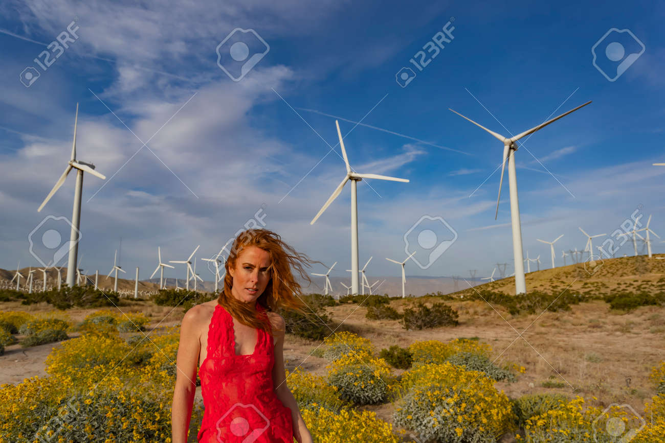 A beautiful redhead model poses outdoors with wind turbines in the background - 121087678