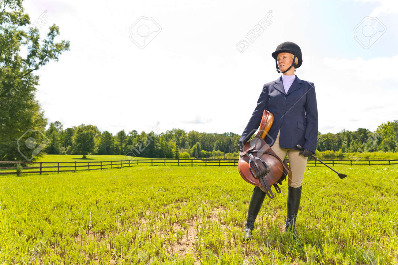 A blonde equestrian model poses outdoors before a horse show - 149928811