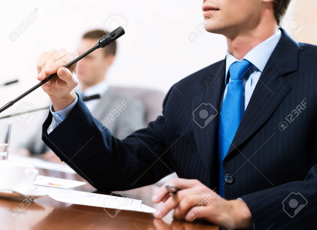 businessman, said into the microphone, in the background colleagues communicate with each other Stock Photo - 16825855