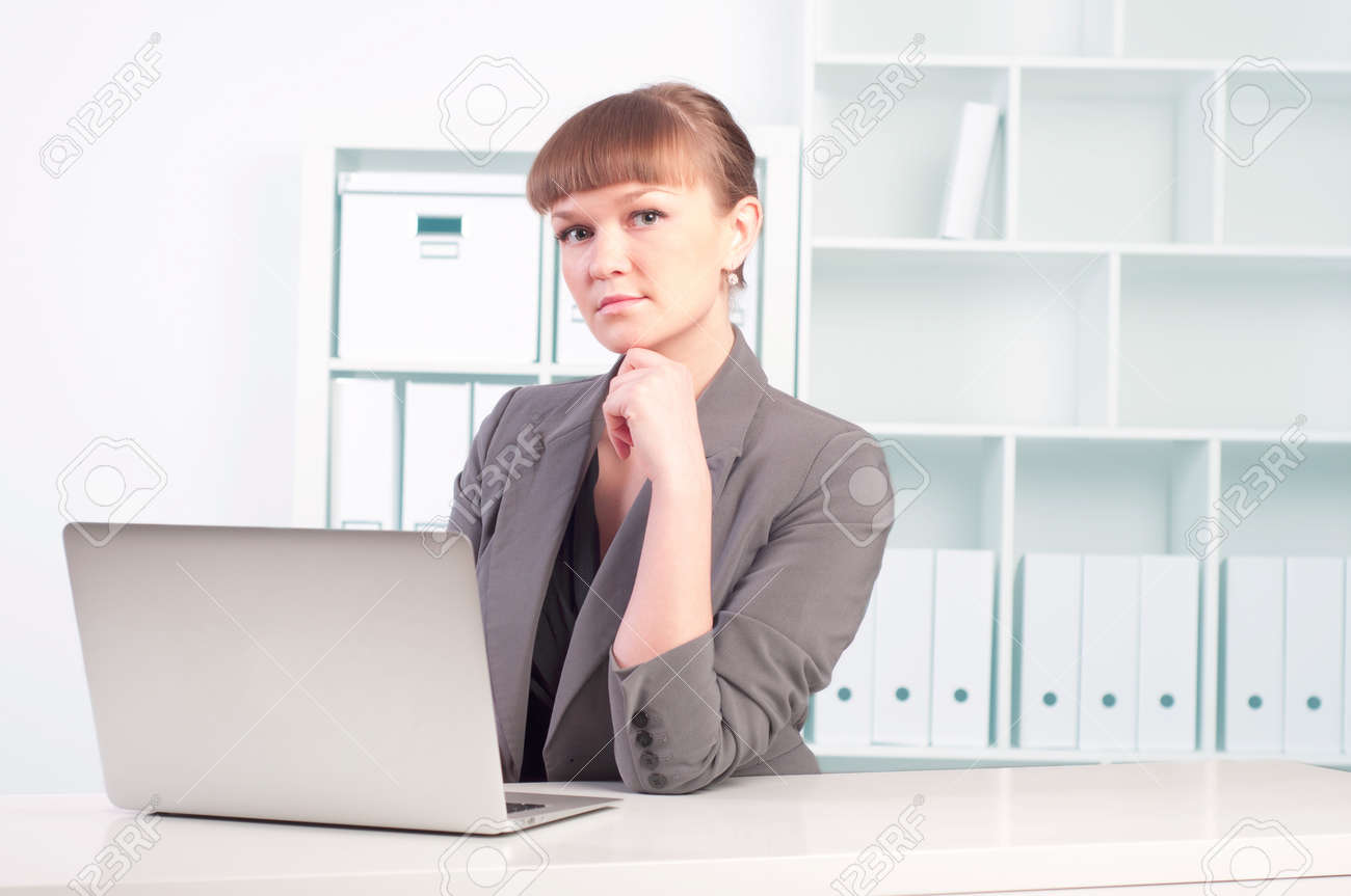 portrait of a beautiful young woman who works at a laptop in the office Stock Photo - 17572951