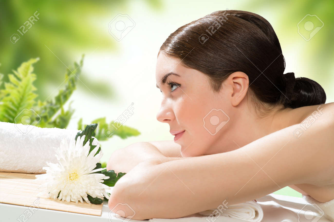 beautiful spa woman lying on the couch, in front of her flower and rolled towel Stock Photo - 19340955