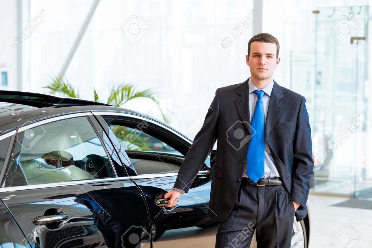 dealer stands near a new car in the showroom, put one hand on the car Stock Photo - 19666173
