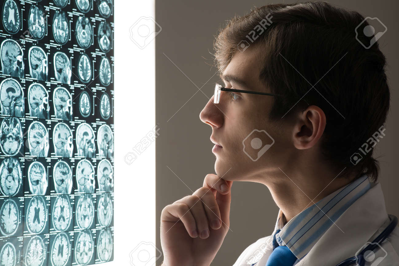 male doctor looking at the x-ray image attached to the glowing screen Stock Photo - 19981768