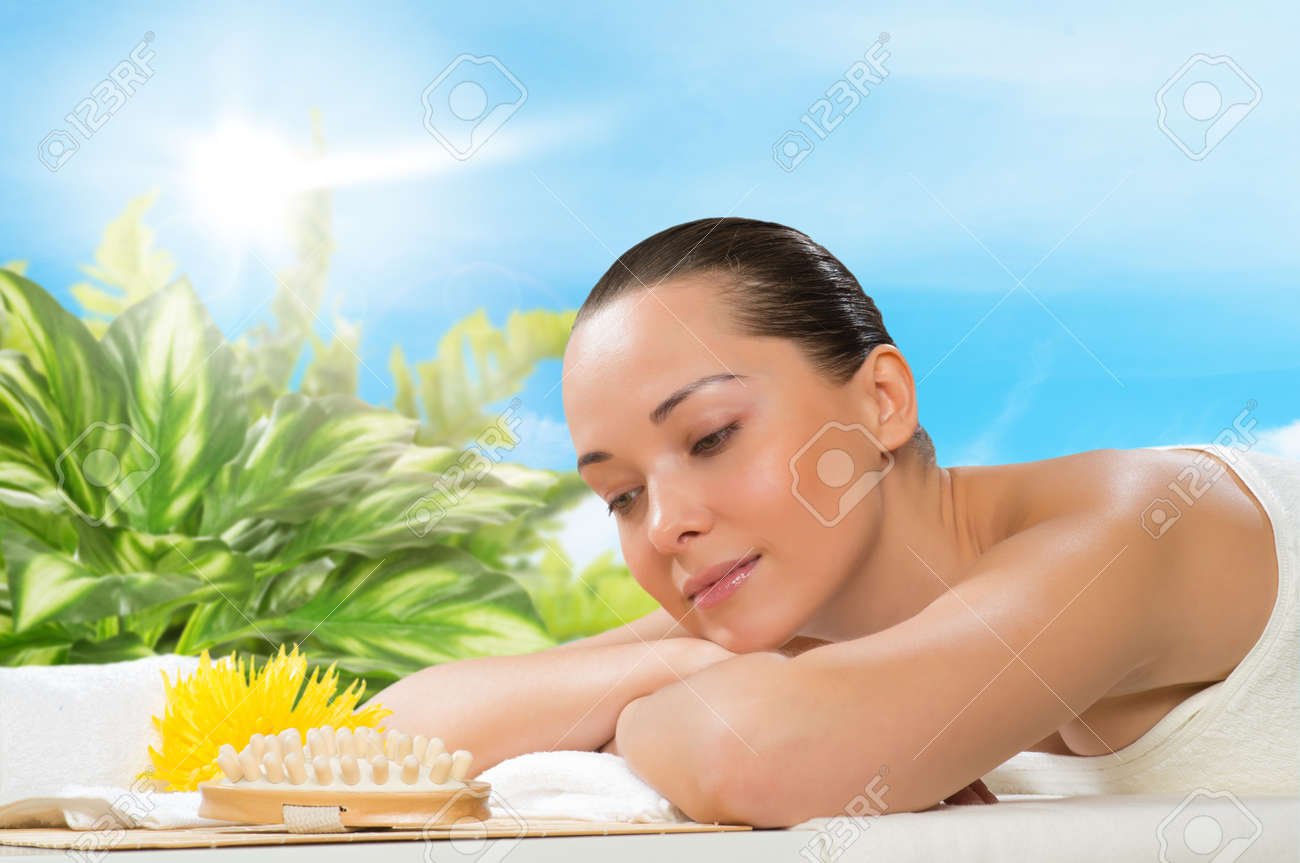 beautiful  woman lying on the couch, in front of her flower and rolled towel Stock Photo - 20075799