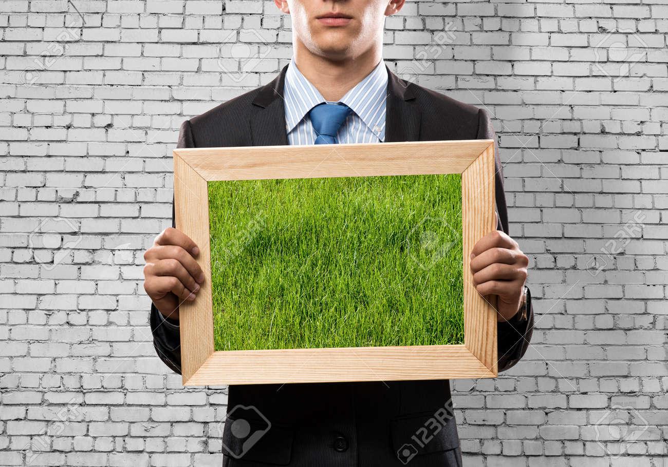 Abschluss Oben Des Geschäftsmannes, Der Rahmen Mit Grünem Gras Hält ...