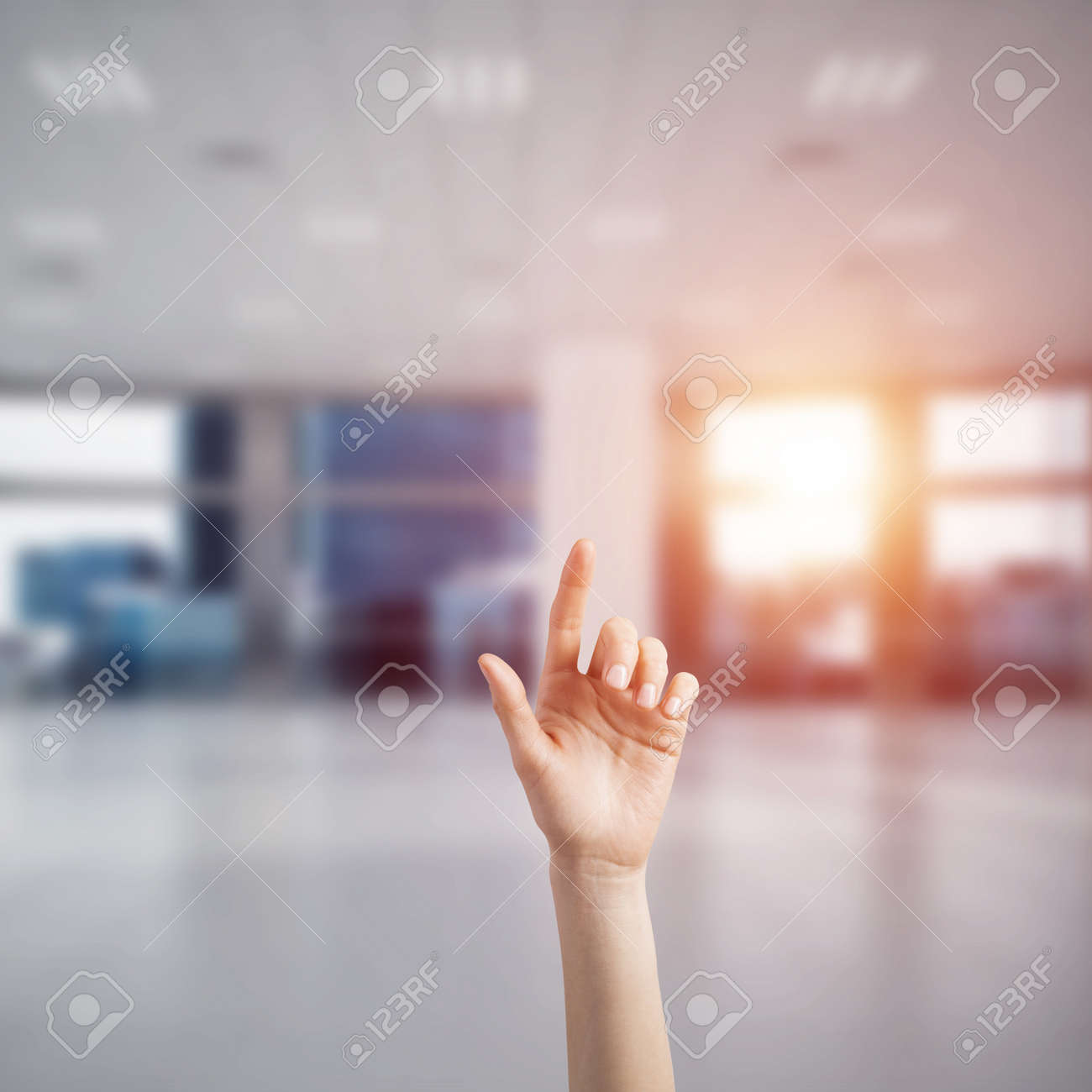 close of woman hand touching screen with finger and office at