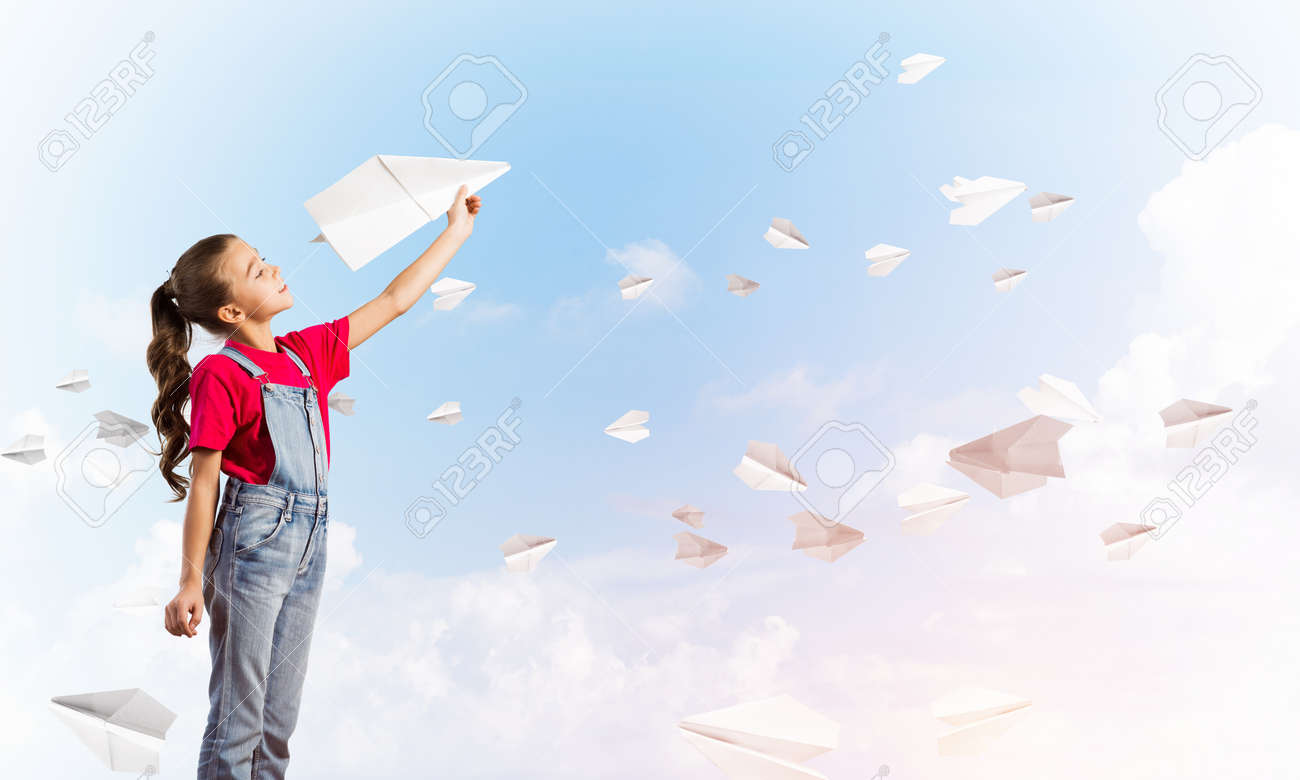 Little Cute Girl Against Sky Background Playing With Paper Airplane Stock Photo Picture And Royalty Free Image Image 94567848