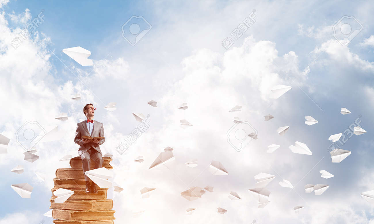 Funny man in red glasses and suit sitting on book and paper planes flying around - 119324609